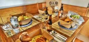Dam Brewery take out meals and to go beers on home table